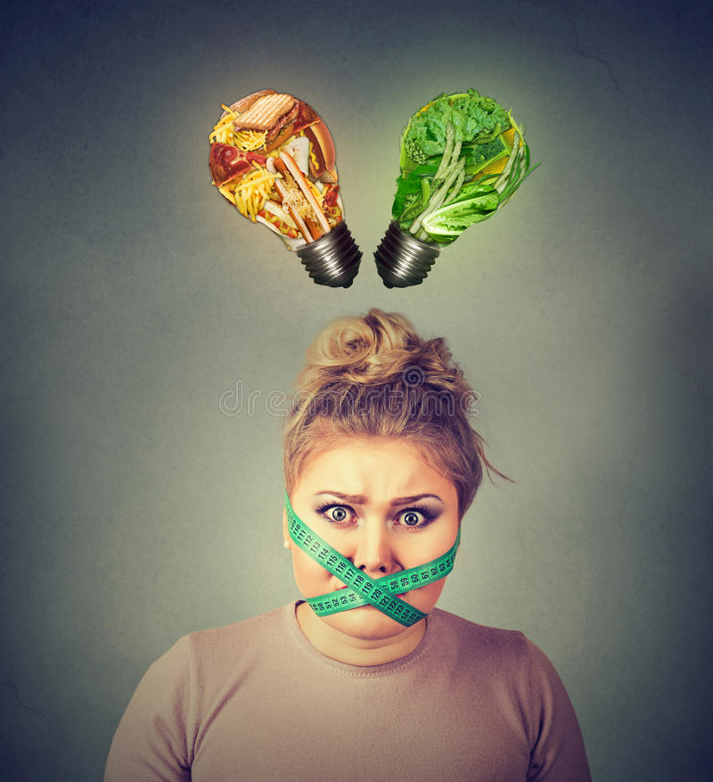 Diet restriction stress. Frustrated woman with measuring tape around her mouth stock photo