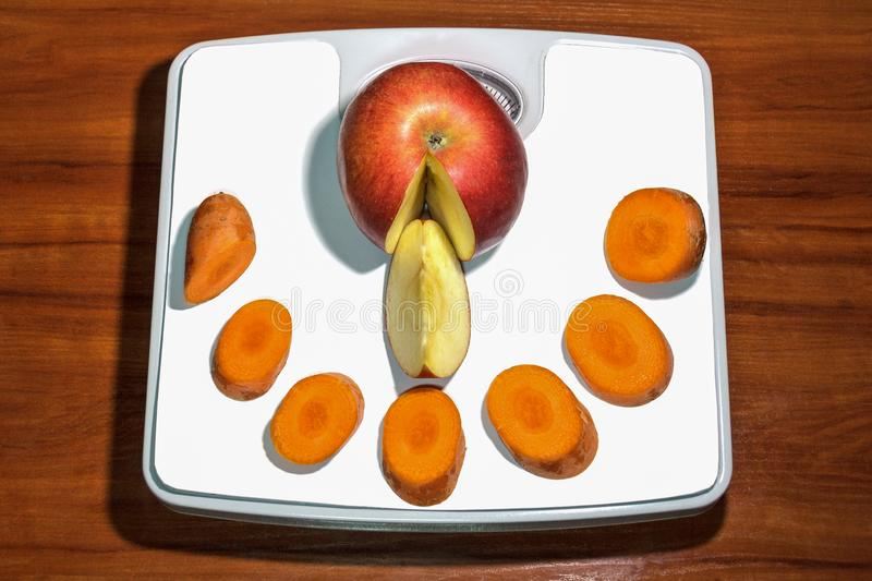 Diet set apple, carrots on scales on a white surface. Diet set apple, carrot on scales for weight loss stock photography