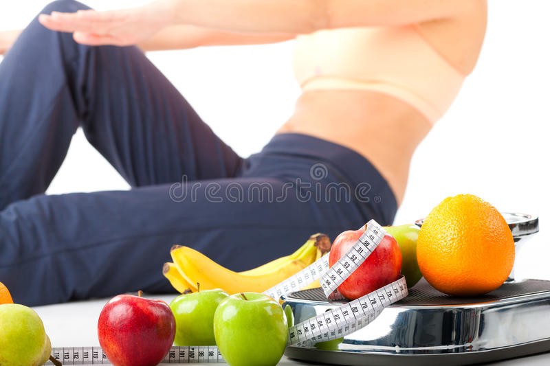 Diet and sport - young woman is doing sit-ups. Next to a measuring scale, a measuring tape and fruits royalty free stock images
