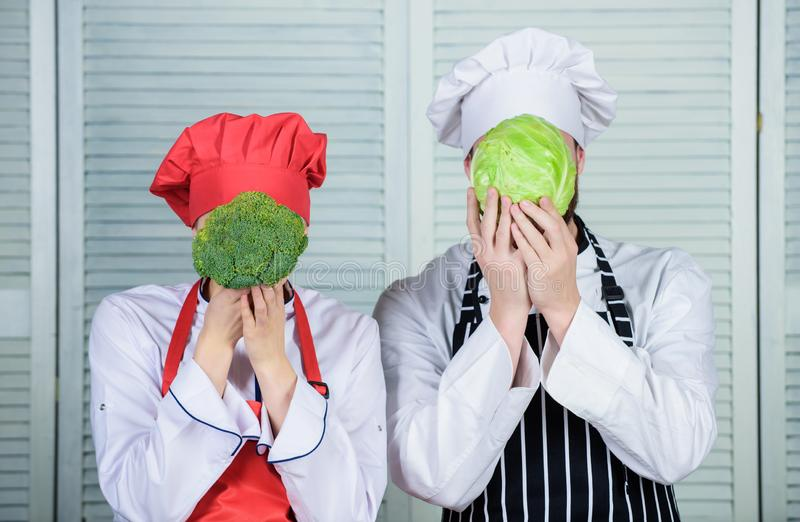 Diet on their mind. Couple cooks hold cabbage and broccoli in front of face. Healthy food concept. Couple cooking royalty free stock image