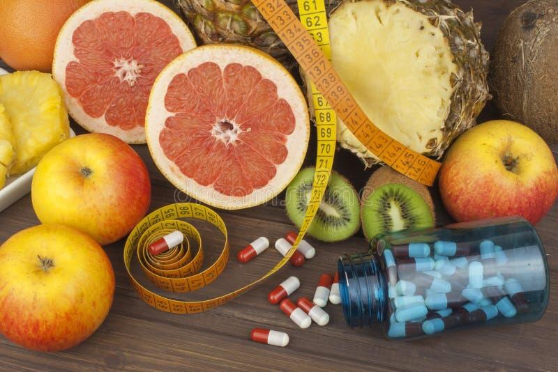 Diet-tillägg för viktförlust Röd grapefrukt och frukt för viktförlust fotografering för bildbyråer