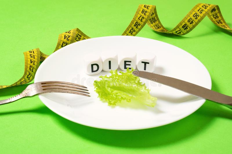 Diet, weigh loss, healthy eating, fitness concept. Small portion of food on big plate. Small green salad leaf on white plate with. Fork and knife and text diet royalty free stock images