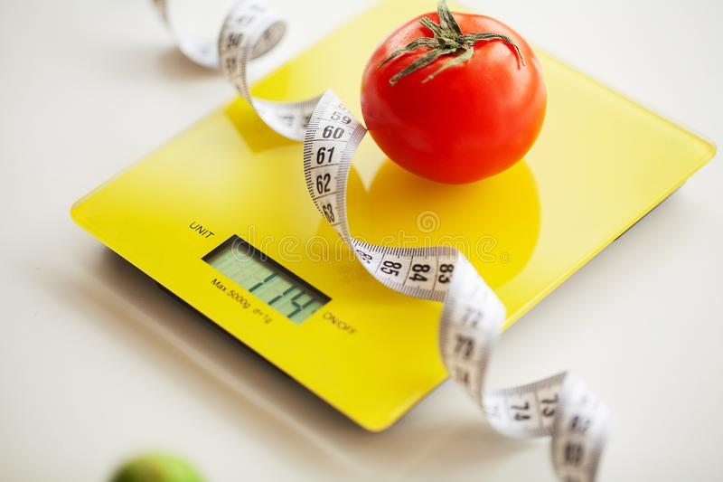 Diet or Weight Control Concept. Fruits and Vegetables With Measuring Tape On Weight Scale. Fitness and Healthy Food Diet. Concept stock photography