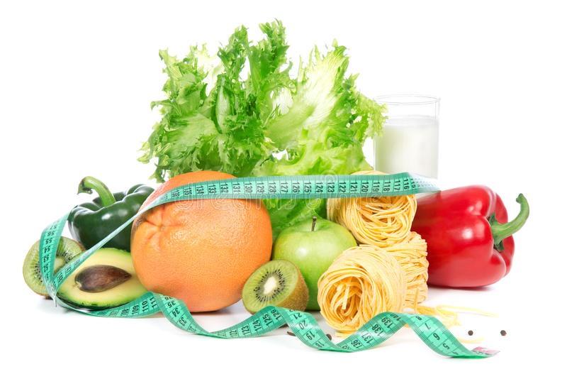 Diet weight loss breakfast concept with tape measur. E organic green and red pepper, tomatoes, almonds, fresh salad, spaghetti, grapefruit, glass of kefir on a stock photos