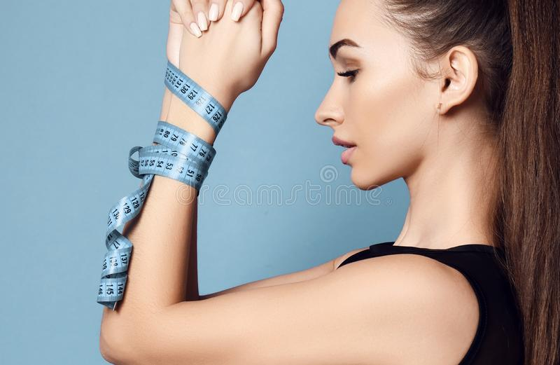 Diet weight loss concept. Pretty sport woman hands tied with a centimeter tape measure stock photo