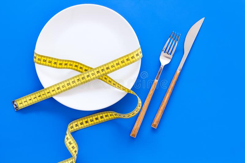 Diet for weight loss concept. Proper nutrition. Medical starvation. Empty plate with fork and knife near measuring tape. On blue background top view stock photography