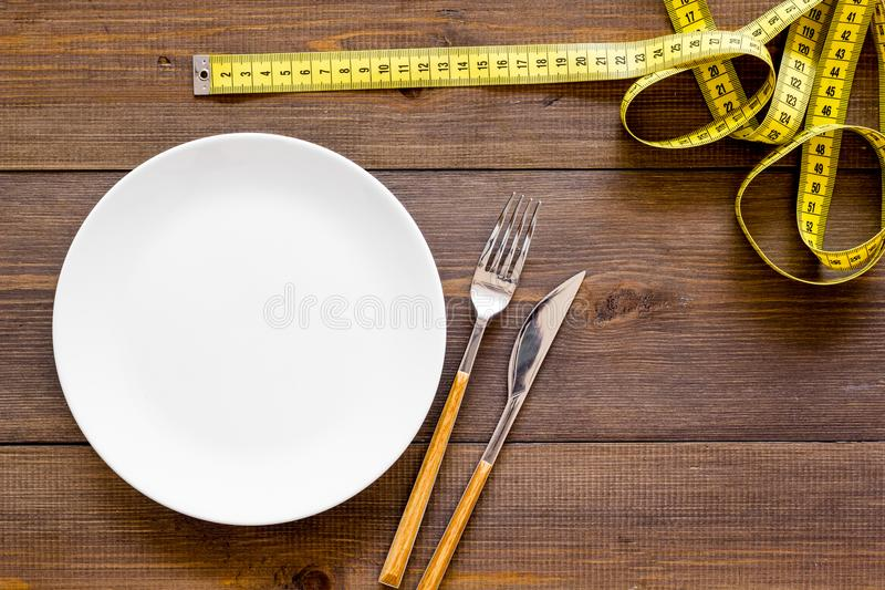 Diet for weight loss concept. Proper nutrition. Medical starvation. Empty plate with fork and knife near measuring tape. On dark wooden background top view stock photos