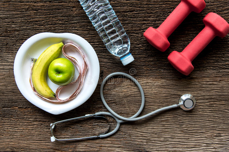 Diet and weight loss for healthy care with medical stethoscope, fitness equipment,measuring tap,fresh water and green apple on woo. Den background top view stock image