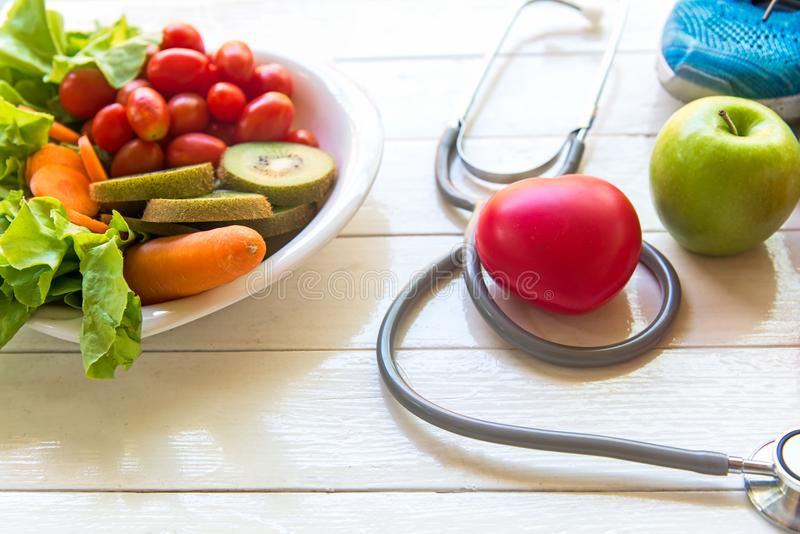 Diet and weight loss for healthy care with medical stethoscope, fitness equipment,. Vegetable salad and healthy food with red heart on the old white wooden stock photos
