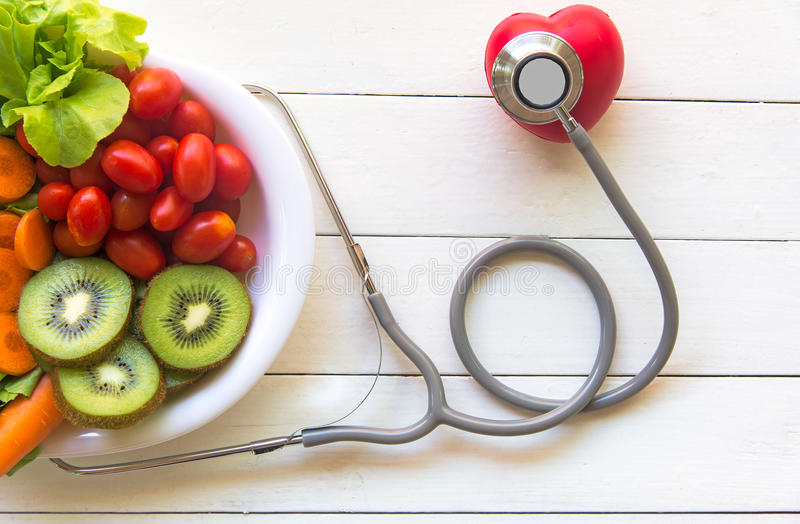 Diet and weight loss for healthy care with medical stethoscope, with red heart and fresh vegetable salad and healthy food on woode. N background top view stock photos