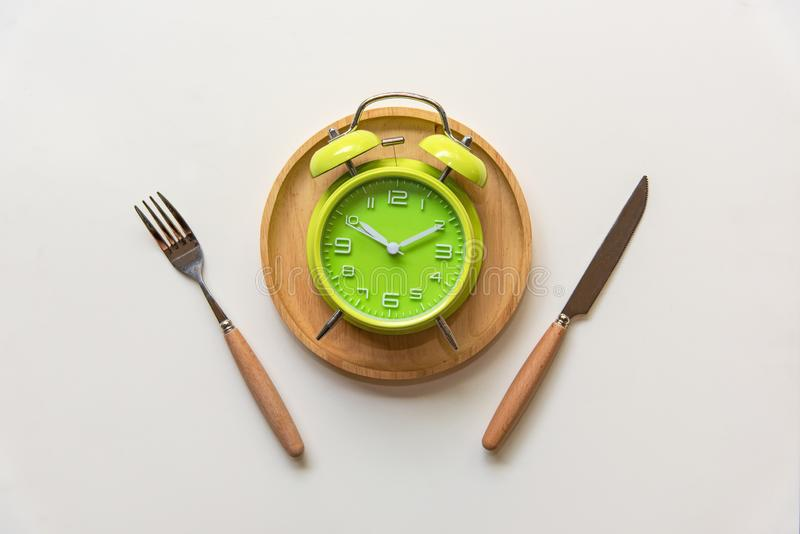 Diet and weight loss for healthy intermittent fasting lunchtime . Alarm clock and plate with cutlery on concrete background. Diet and Healthy Concept royalty free stock photography