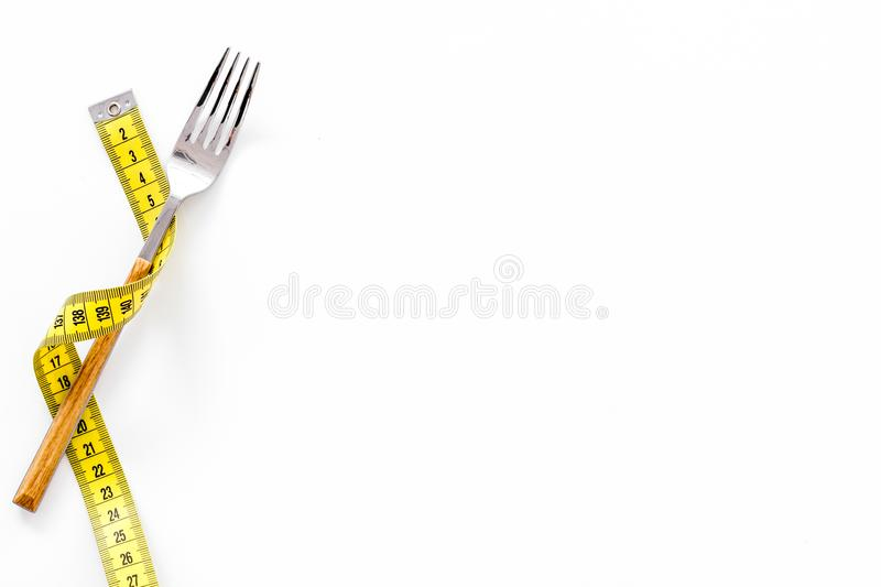 Diet, weight loss, slimming concept. Fork with wound measuring tape on white background top view space for text stock image