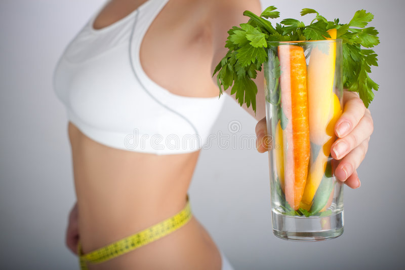 Diet Woman. Concept image of a woman holding a glass of vegetables in front of her body stock image