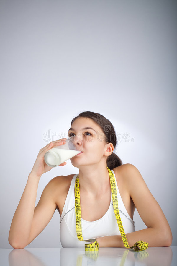 Diet Woman. Woman drinking a glass of milk looking up stock image