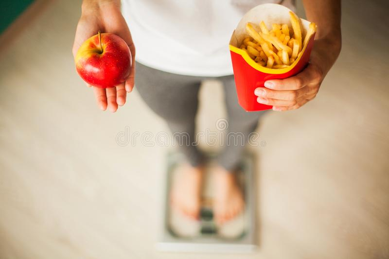 Diet. Woman Measuring Body Weight On Weighing Scale Holding Unhealthy Junk Food. Weight Loss. Obesity. Top View royalty free stock photography