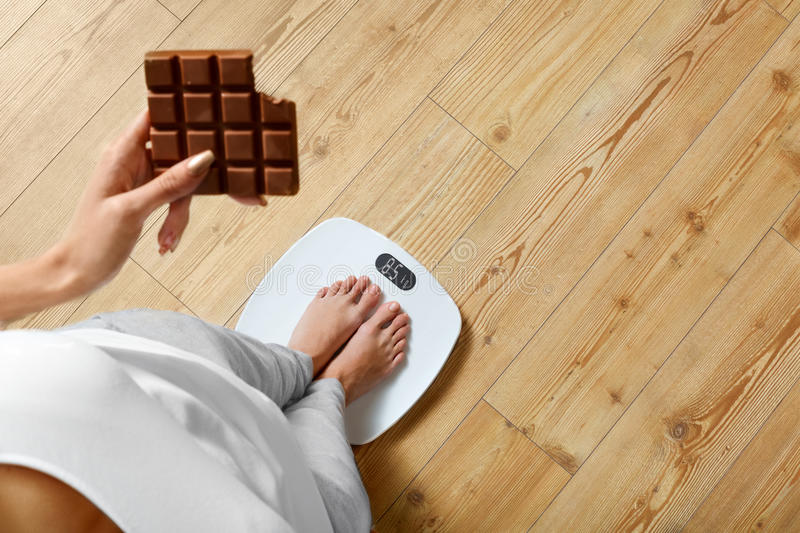 Diet. Woman On Weighing Scale, Chocolate. Unhealthy Food. Weight. Diet. Young Woman Standing On Weighing Scale And Holding Chocolate Bar. Sweets Are Unhealthy stock image