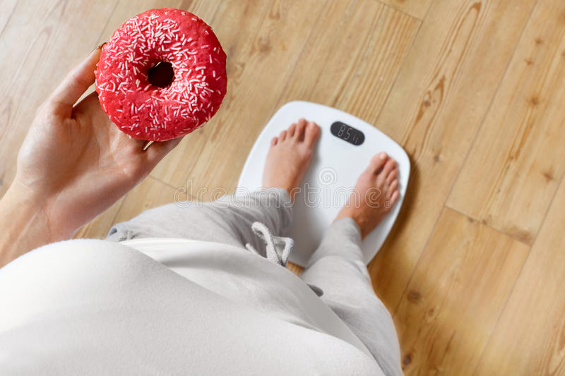 Diet. Woman On Weighing Scale, Holding Donut. Unhealthy Food. Ob. Diet. Woman Measuring Body Weight On Weighing Scale Holding Donut. Sweets Are Unhealthy Junk stock images