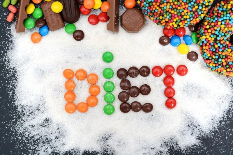 Diet word written with colorful candies on sugar powder stock image