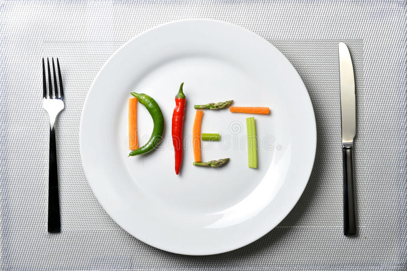 Diet written with vegetables in healthy nutrition concept. Diet written with vegetables in healthy nutrition and dieting resolution concept on silver dish mat royalty free stock photo