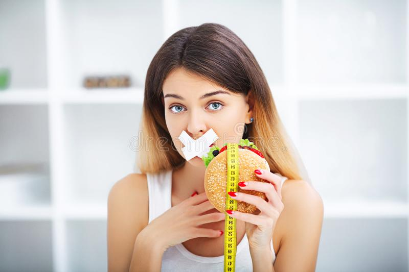 Diet. Young beautiful woman eating burger, It`s junk and unhealt. Hy food, Beauty face natural makeup royalty free stock photography