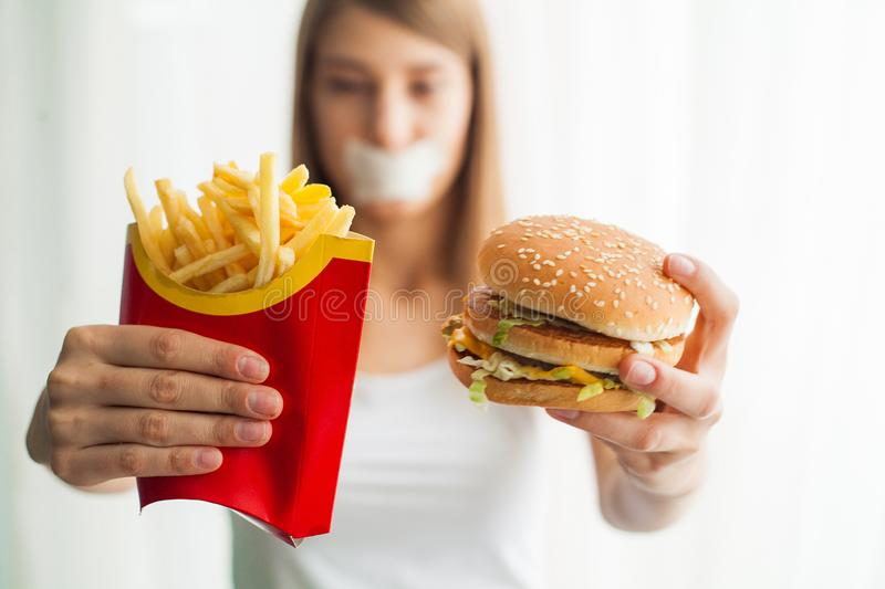 Diet. Young woman with duct tape over her mouth, preventing her to eat junk food. Healthy eating concept stock photos