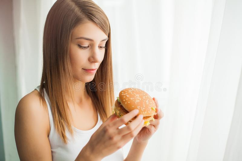 Diet. Young woman with duct tape over her mouth, preventing her to eat junk food. Healthy eating concept royalty free stock image