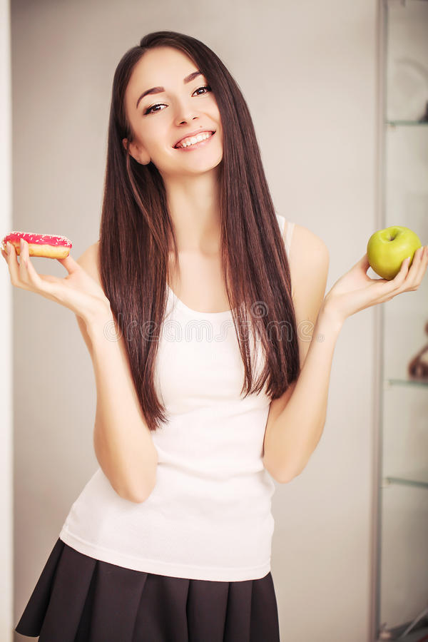 Diet. A young woman holding a pizza on the scales and make a choice between an apple and a donut. The concept of healthy eating stock photo