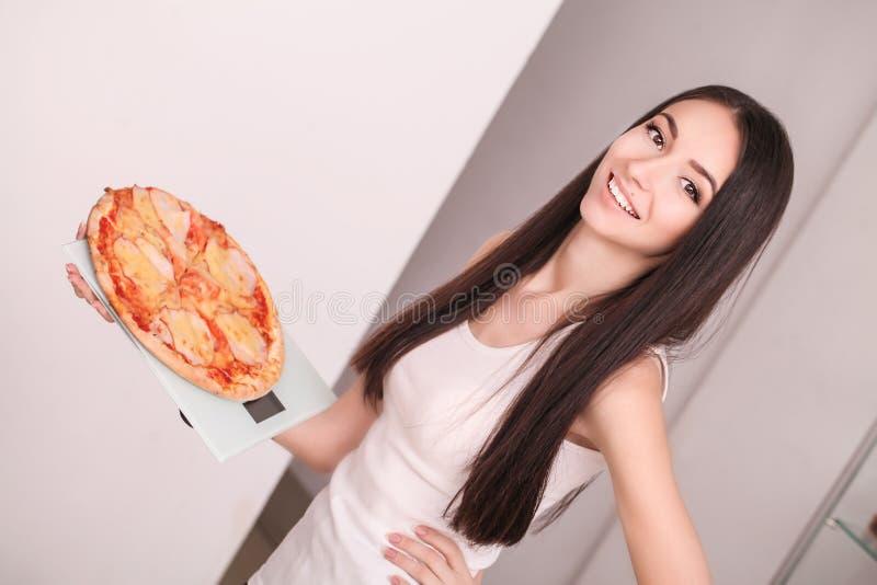 Dieta Balanza de la muchacha hermosa joven que celebra la pizza La estafa imagen de archivo