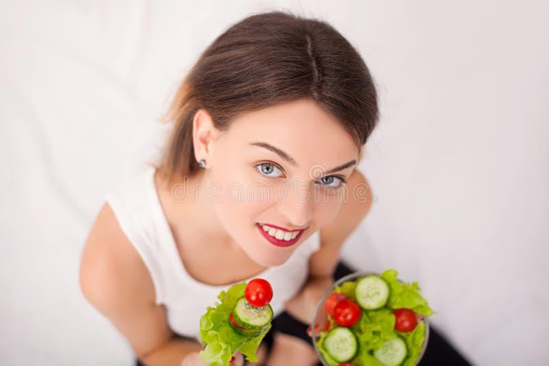 Dieta Bella giovane donna che mangia insalata di verdure fotografie stock libere da diritti