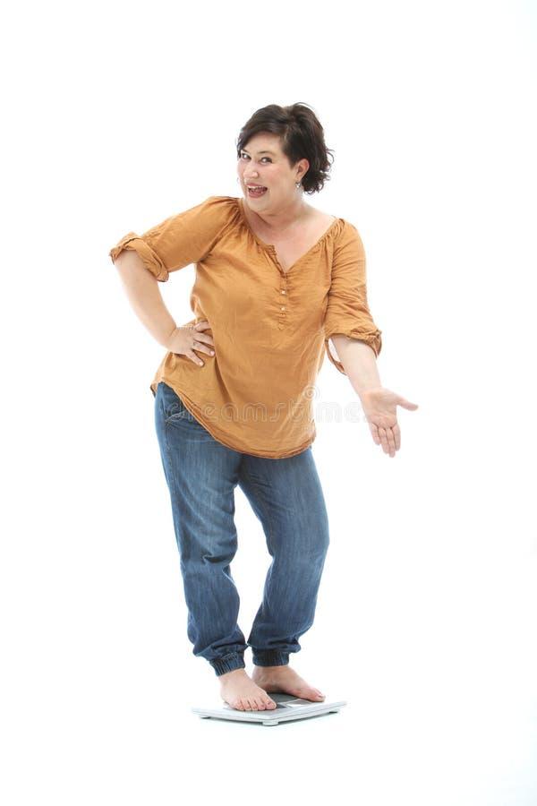Dieta bem sucedida - a mulher em uma escala é orgulhosa imagem de stock royalty free
