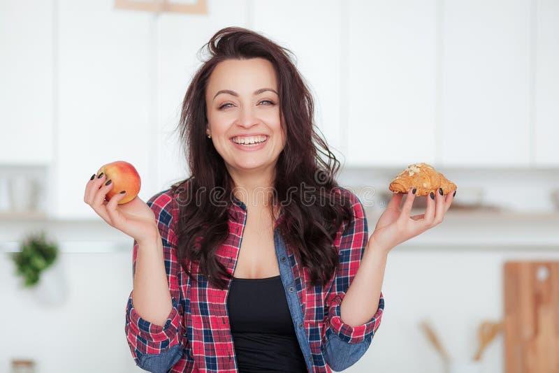 Dieta Concepto de dieta Alimento sano Mujer joven hermosa que elige entre las frutas y los dulces Pérdida de peso imagen de archivo libre de regalías