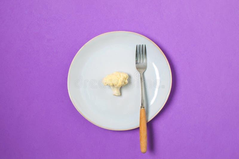 Dieta, concetto minimo di perdita di peso, cibo sano - cavolfiore sul piatto, spazio della copia, fondo porpora fotografie stock
