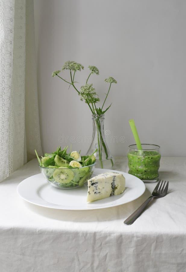Dieta cruda sana del desayuno fresco verde Color brillante del smoothie del Detox Queso verde y ensalada Materia textil blanca rú foto de archivo libre de regalías