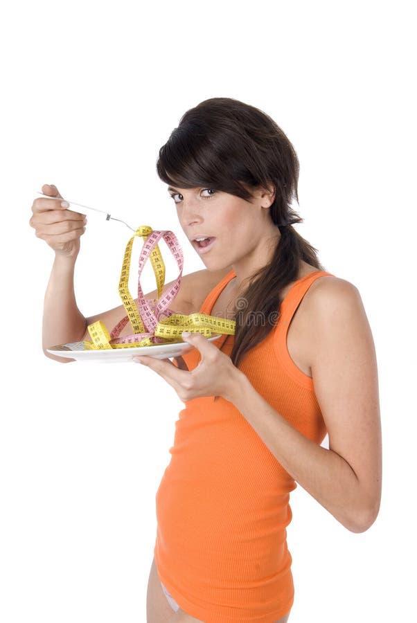 Dieta da mulher que come uma medida de fita fotografia de stock royalty free