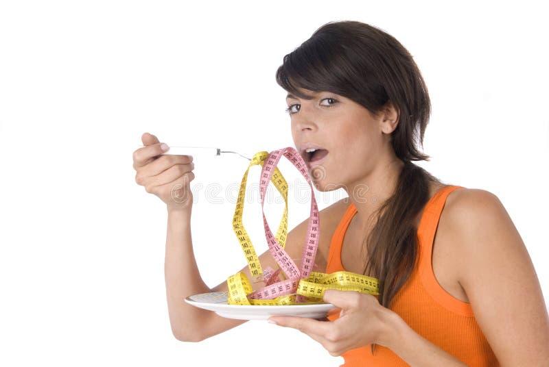 Dieta da mulher que come uma medida de fita isolada imagem de stock royalty free