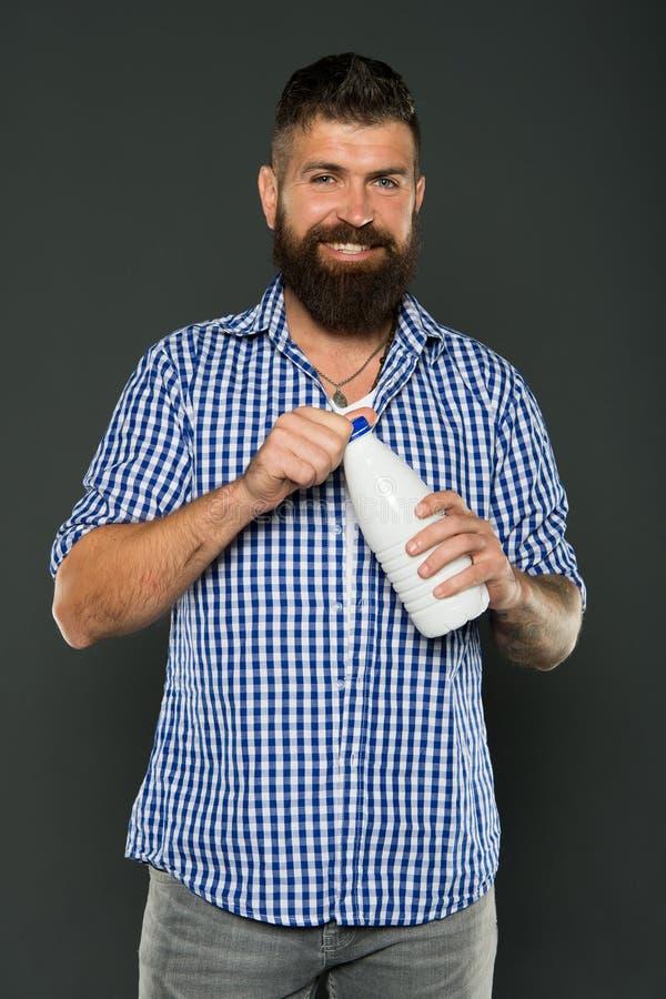 Dieta del lattosio Bottiglia bianca della tenuta barbuta dell'uomo con latte Latte caucasico brutale della bevanda dei pantaloni  immagini stock