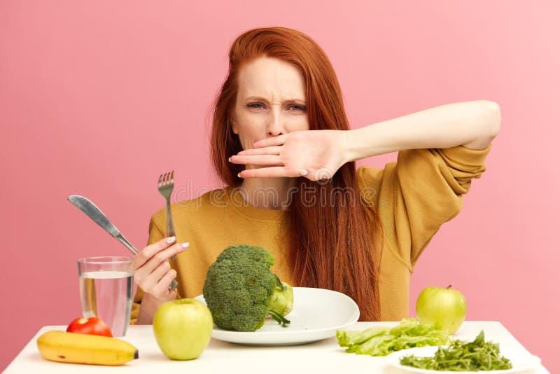 Dieta di verdure Broccoli smussati tristi della tenuta della donna sulla forcella mentre facendo smorfia immagine stock libera da diritti