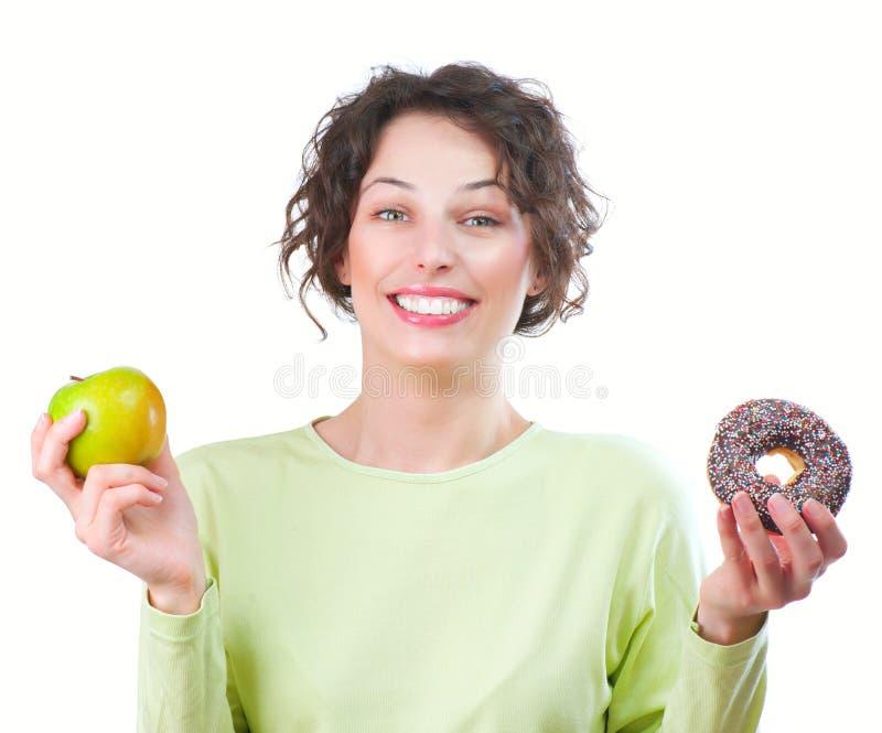 Dieta. Donna che sceglie fra la frutta e la ciambella fotografie stock