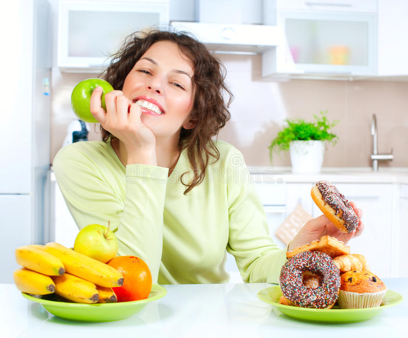 Dieta. Donna che sceglie fra la frutta ed i dolci immagini stock libere da diritti