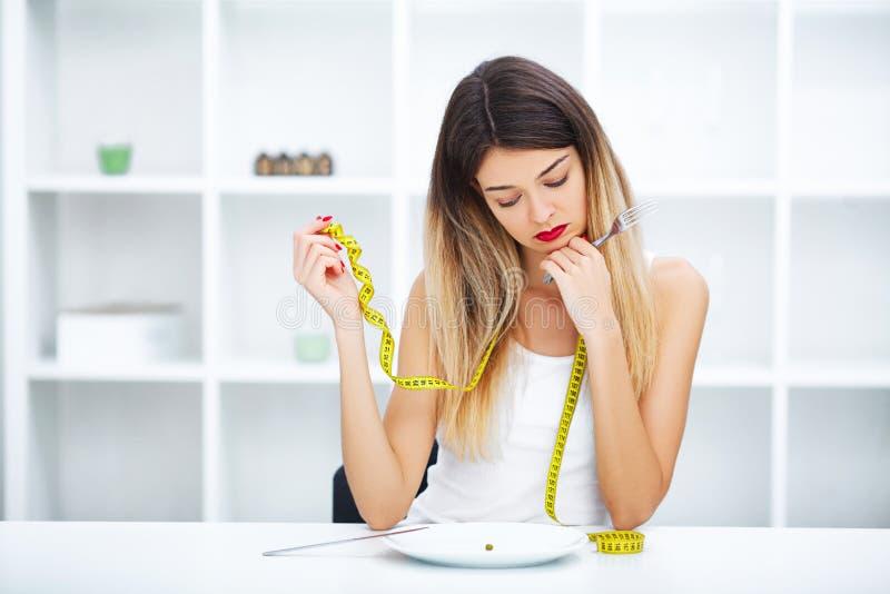 Dieta Dieta dura - cibo severo La ragazza sta tenendo un piatto e sta provando a mettere immagini stock