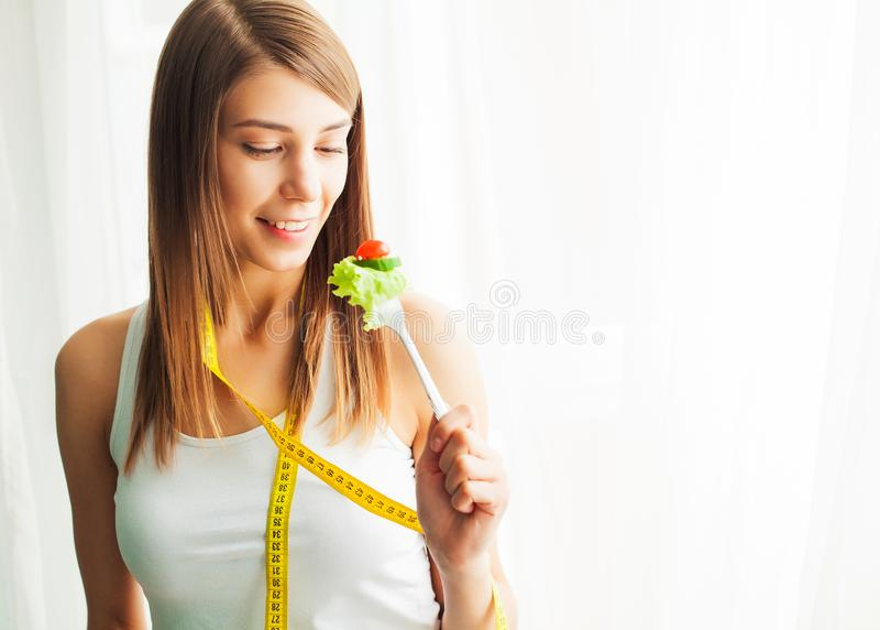 Dieta e comer saud?vel Jovem mulher que come a salada saud?vel ap?s o exerc?cio imagem de stock royalty free