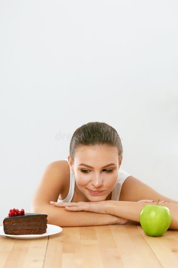 Dieta e nutrition Mulher que escolhe entre o bolo e o Apple fotos de stock royalty free