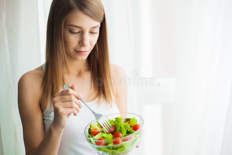 Dieta e saúde Jovem mulher que come o alimento saudável após o exercício imagens de stock royalty free