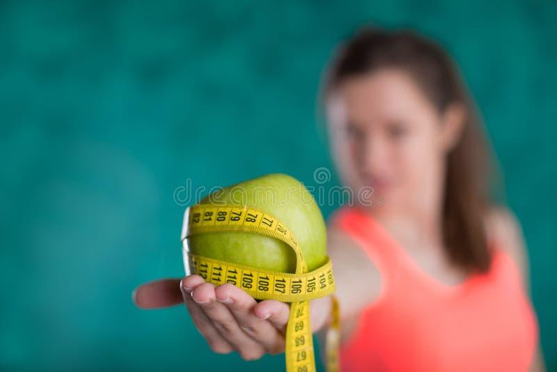 Dieta Fêmea feliz saudável com maçã e fita métrica para o conceito da perda da dieta e de peso - isolado no fundo de turquesa fotos de stock
