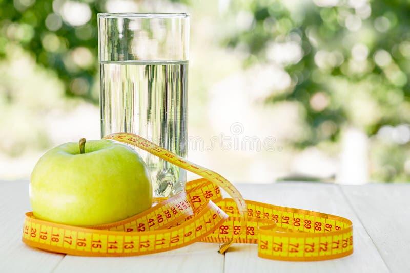 dieta Jabłko z wodną i pomiarową taśmą na białym drewnianym stole na zielonym naturalnym tle tło zamazywał opieki pojęcia twarzy  fotografia royalty free