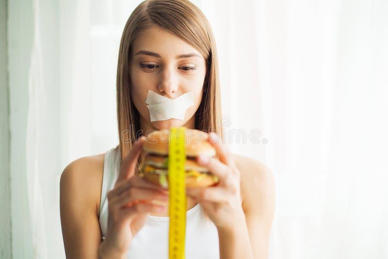 Dieta Jovem mulher com a fita adesiva sobre sua boca, impedindo a para comer a comida lixo Conceito saudável comer fotografia de stock royalty free