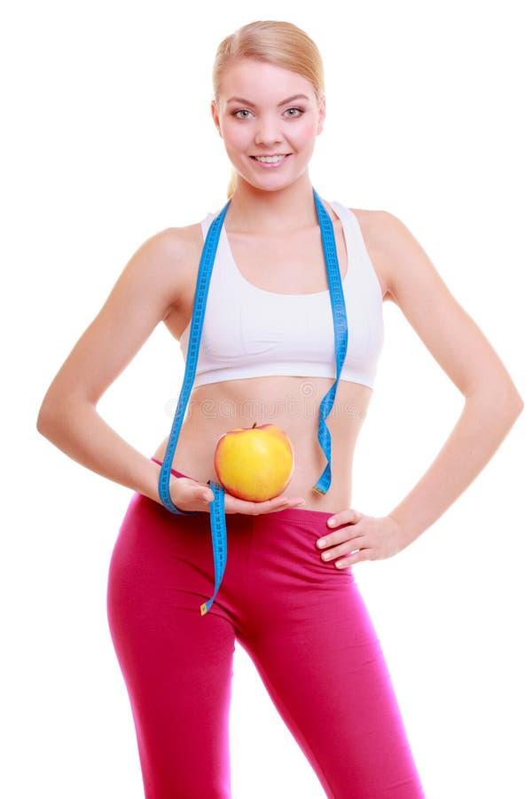Dieta. A menina apta da mulher da aptidão com medida da fita e a maçã frutifica imagem de stock royalty free