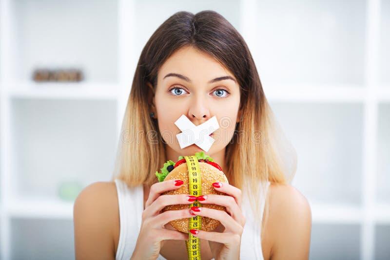 Dieta Mujer hermosa joven que come la hamburguesa, lo desperdicios del ` s y el unhealt imagenes de archivo
