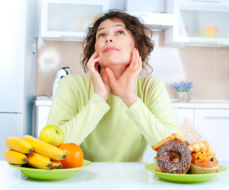 Dieta. Mujer que elige entre las frutas y los dulces imagenes de archivo