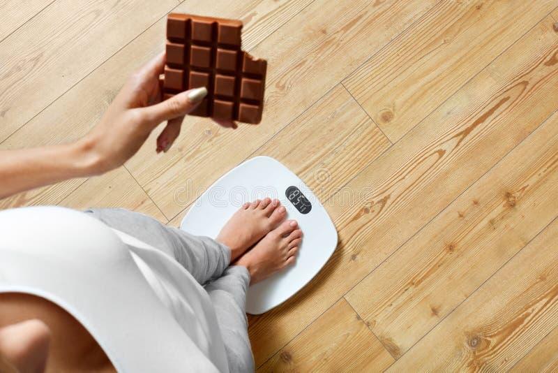 Dieta Mulher na escala de peso, chocolate Alimento insalubre peso imagens de stock royalty free